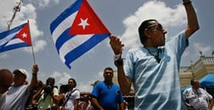 """A man waves a Cuban flag and shouts """"Viva Cuba libre"""" in front of Versallies Restaurant in Little Havana. Photograph: Chip Somodevilla/Getty Images"""