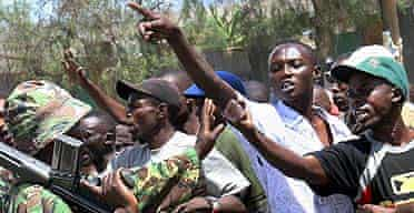 A gang of youths belonging to the Kikuyu tribe confront an armed policeman in the Kenyan Rift Valley province
