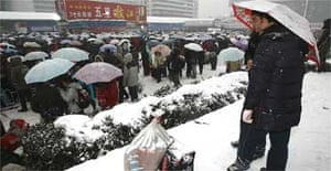 Stranded passengers queue in snow at Wuhan in China's Hubei province
