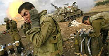 Israeli soldiers cover their ears as an artillery unit fires shells towards southern Lebanon