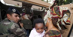 A French soldier helps a mother and her daughter in Chad