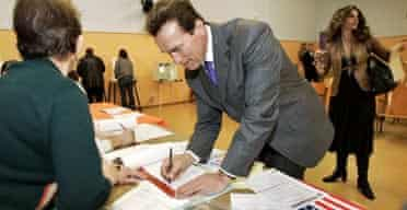 Arnold Schwarzenegger and Maria Shriver sign in before casting their votes in Los Angeles. Photograph: Al Seib-Pool/Getty Images