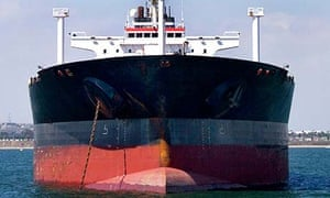 A large cargo ship sits at anchor in the calm waters of a safe harbour
