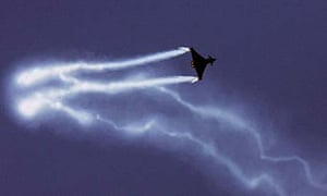 The BAE Eurofighter Typhoon military jet plane leaves smoke trails at an air show in Paris