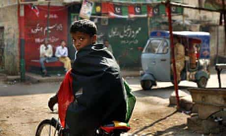 A boy wrapped in a flag of the Pakistan People's Party rides his bike past campaign posters on a street in Karachi, Pakistan