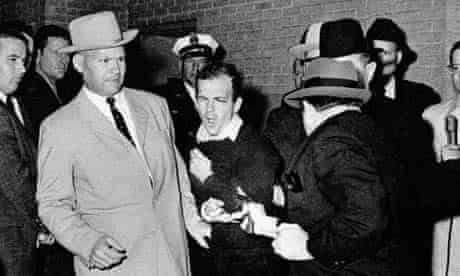 Lee Harvey Oswald, accused assassin of US president John F. Kennedy, reacts as Dallas night club owner Jack Ruby, foreground, shoots at him from point blank range in a corridor of Dallas police headquarters in 1963. The plainclothesman at left is Jim A. Leavelle