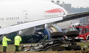 Workers inspect the British Airways plane that crash-landed at Heathrow