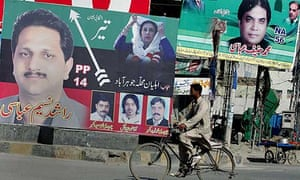 A cyclist rides past a billboard showing a portrait of slain opposition leader Benazir Bhutto, centre, and former prime minister Nawaz Sharif, top, displayed along a roadside in Rawalpindi, Pakistan