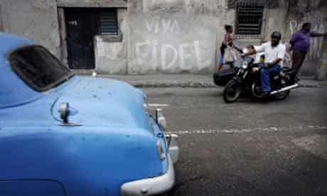 Cubans watch a vintage car pass in Havana