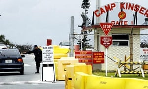 A guard checks a motorist at the entrance of Camp Kinser, a US marine corps base in Urasoe, Okinawa, Japan