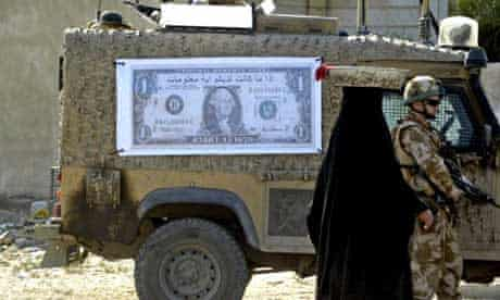 """An Iraqi woman walks past a British soldier and military vehicle with a poster of a dollar bill with the Arabic writing: You can get some money, in exchange for some information"""". Photograph: Essam al-Sudani/AFP/Getty Images"""