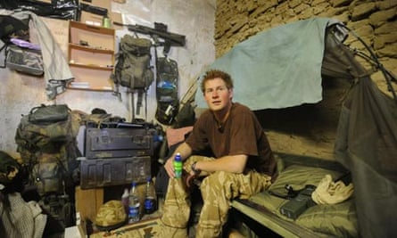 Prince Harry sits on his camp bed in his accommodation