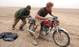 Prince Harry tries to push start an abandoned motorcycle in the desert, with the help of 'Max' his Fijian tank driver, in Helmand province, Afghanistan.