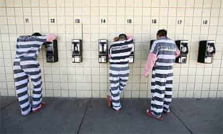 Inmates talk on pay phones at a jail in Phoenix, Arizona