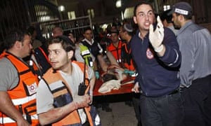 A wounded man is evacuated by Israeli medics following last night's shooting at the Mercaz Harav yeshiva or seminary in Jerusalem