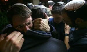 Israeli Jewish students comfort each other in the Merkaz Harav Yeshiva