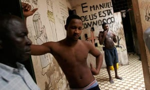 Police officer Sadio Corobo, left, walks past prisoners housed in the basement of a crumbling colonial villa in Bissau, Guinea-Bissau, July 17, 2007