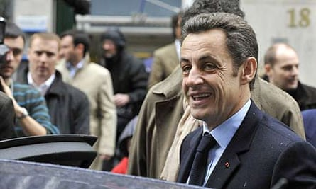 French president Nicolas Sarkozy leaves the polling station in Paris after the first round of the municipal elections