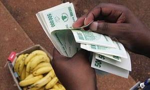 A man counts a big stack of money to buy some bananas in Harare, Zimbabwe