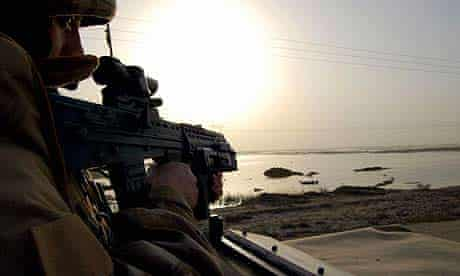 A British soldier patrols the northern suburbs of the southern Iraqi city of Basra