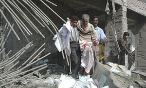 Rescuers help a wounded man from the ruins of a government office in Lahore following twin bombings in which at least 20 people died
