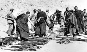Tibetan monks, surrounded by Chinese soldiers, lay down their arms in the mountains after an unsuccessful uprising against Chinese rule that led to the exile of the Dalai Lama