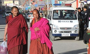 Buddhist monks walk past police cars near the Labrang monastery in the Tibetan town of Xiahe