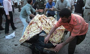 Iraqis evacuate bodies from the site of a suicide attack in the Shia holy city of Karbala.