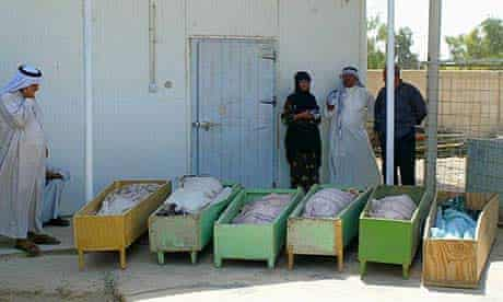 People gather at the Baquba hospital morgue next to caskets containing the bodies of six of their family members who were killed by a roadside bomb south of Baquba, Iraq