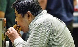 A man eats a humburger at a fast-food restaurant in Narita, Japan.