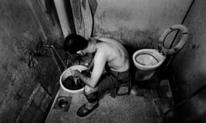 Muntaser, a young Iraqi refugee, washes his clothes in a shared toilet in the area of Sad el-Bousharya, Beirut