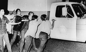 Demonstrators attempt to push over a Chicago Police Department vehicle during the anti-Vietnam War protests surrounding the 1968 Democratic National Convention, Chicago, Illinois, August 28, 1968