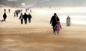 Walkers get caught in a sand and hail storm on Tynemouth beach, Tyne and Wear in the north east of England