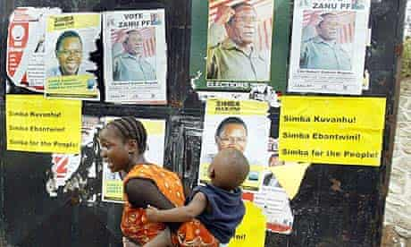 A woman walks past election posters in Mutare, Zimbabwe