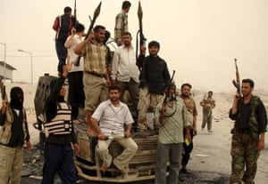 Fighters loyal to Shiite cleric Moqtada al-Sadr pose with their weapons next to a burned Iraqi police vehicle following clashes in Basra