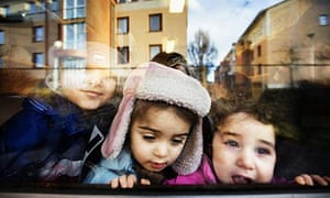 Three immigrant children look through a window at a daycare in the town of Soedertaelje, south of Stockholm