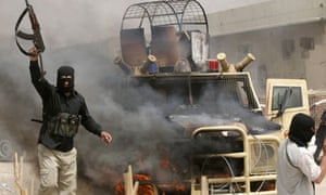 Mahdi Army fighters gesture as they stand next to a burning Iraq armored police vehicle