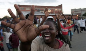 A supporter of Movement for Democratic Change raises her hand in the party's five fingered salute during celebrations in Harare as preliminary election results came in yesterday