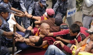 Nepalese police officers detain Tibetan exile protesters demonstrating against the alleged oppression by Chinese authorities