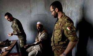 Two Nato medics examine an Afghani citizen