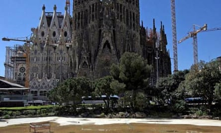A tourist walks through what is barely a puddle in the Sagrada Familia Lake