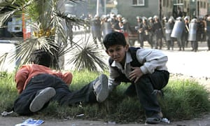 Children duck as police fire teargas during clashes with protesters north of Cairo