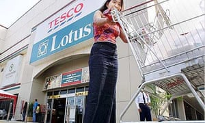 A woman pushes a trolley past the entrance of a Thai outlet of the British supermaket chain Tesco Lotus in Bangkok
