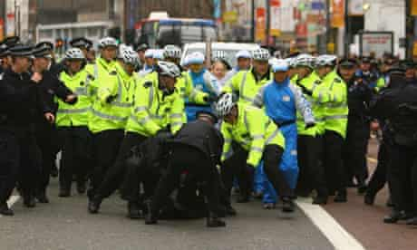 Police officers restrain a protester during the relay of the Olympic torch in London.