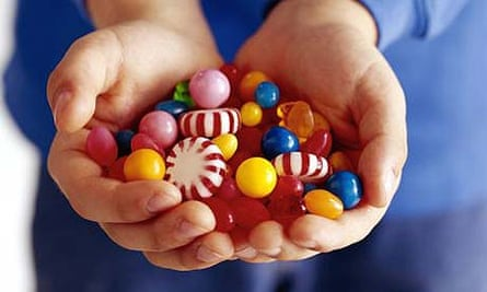 A child holding lots of sweets