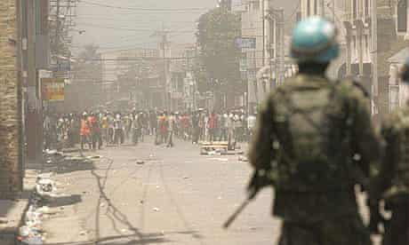 Haitian rioters block a street in downtown Port au Prince while Brazilian UN peacekeepers look on.