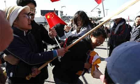 A man carrying a Tibetan flag is attacked by pro-China supporters awaiting the start of the Olympic torch relay in San Francisco