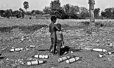 Two young boys are surrounded by spent rocket bombs in Jessore, Bangladesh, in 1971