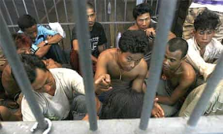 Burmese illegal migrant workers rescued from a cramped container sit in a prison cell at a police station in Ranong province, south of Bangkok