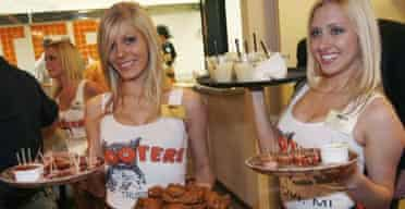Waitresses serve food and beverages at the opening celebration of the first Israeli branch of Hooters restaurants in Netanya, near Tel Aviv